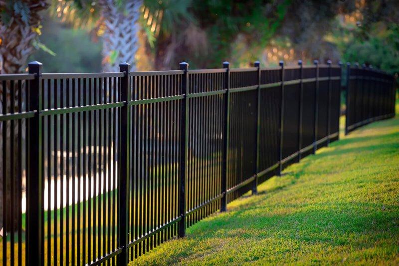Czarne ogrodzenie metalowe ze zdobieniami